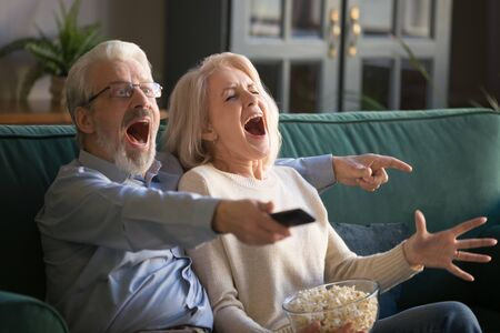 Senior middle aged positive couple supporting cheering favorite sport team, watching football or basketball match on TV set. Elderly husband and wife having fun celebrating victory at home on sofa.