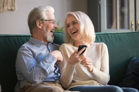 Happy aged husband and wife laughing, having fun at home, using smartphone for ecommerce shopping, watching funny videos, movies or photos, looking at each other, spending time together in living room Foto de archivo - 129610270