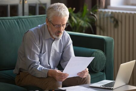 Focused grey-haired elderly man sit on couch reading bank notifications calculating domestic expenditures, concentrated modern mature male consider financial paperwork, pay bills on laptop online