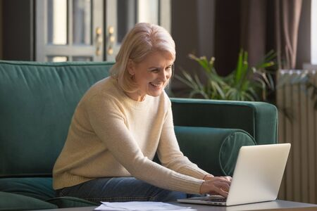 Happy senior beautiful woman work on laptop with easy access or usage, browsing internet, smiling contemporary elderly female using computer at home, typing texting on web, learn new technologies