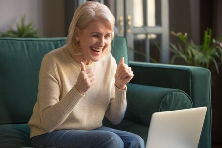 Excited elderly modern woman use laptop feel euphoric receive positive bank feedback in email letter, overjoyed senior female, mature grandmother smile show thumbs up winning online lottery