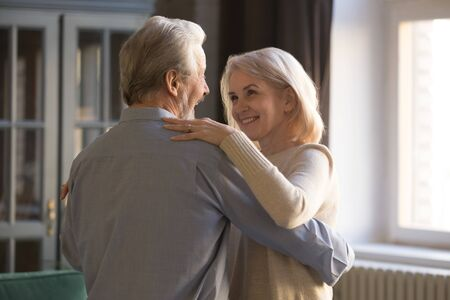 Smiling mature husband and wife relax dancing celebrating wedding anniversary at home, happy elderly man and woman couple waltz sway enjoy romantic tender moment together, relationships goal concept