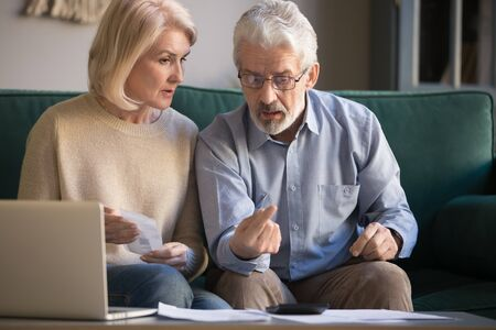 Concerned elderly husband and wife use calculator machine calculate household expenditures work with paperwork, focused senior retired spouses pay bills online, take care of paper documents at home Stock fotó