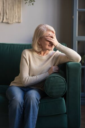 Upset elderly woman sit on couch feel sad disappointed crying over family problems, lonely senior female, mature grandmother mourning grieving for late husband at home, loneliness concept 版權商用圖片