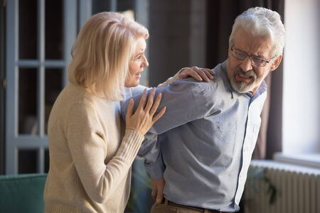 Mature supportive wife help embrace hurt elderly husband suffering from spinal spasm or strain, senior woman hug take care of sick retired man spouse having sudden backache, health problem concept Reklamní fotografie