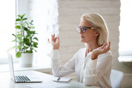 Peaceful concentrated senior businesswoman sit at office desk meditating at workplace, calm focused aged woman worker with mudra hands practice yoga manage emotions. Stress free concept