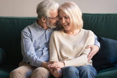 Middle aged gray-haired relaxed caring man hugging senior smiling happy blonde wife, supporting, holding hands, expressing love, tenderness, leaning head to head, sitting on sofa, resting at home.