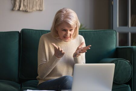Angry elderly woman feel nervous confused with slow internet connection while working on laptop in living room, frustrated mature female get mad having operational software problems on computer