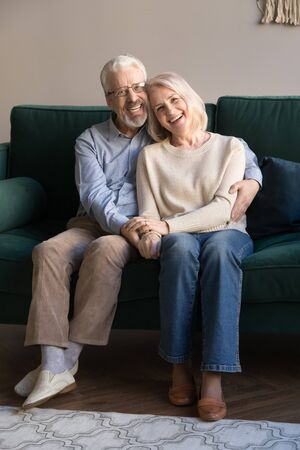 Portrait of happy smiling satisfied elderly husband and wife, looking in camera. Grey-haired retired family couple hugging, holding each other hands, sitting on sofa, relaxing, spending time at home.