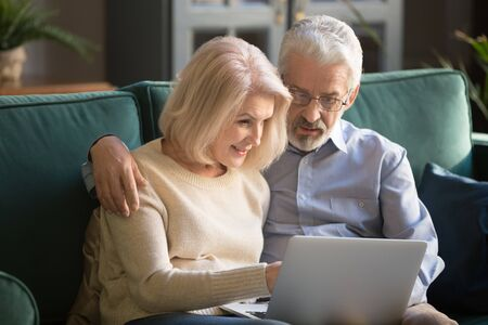Smiling elderly grey-haired couple siting on sofa at home, looking in computer, watching family photos, resting, spending free time in living room. Attractive aged woman helping husband with new app