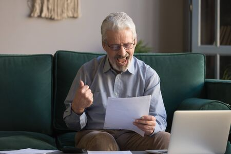 Excited mature man read paperwork feel happy receive bank credit or loan, contemporary elderly male managing domestic finances, get pleasant good news in post correspondence, insurance approval