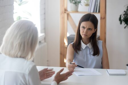 Unhappy millennial recruiter or HR agent look frustrated talking with job applicant during interview in office, doubtful young female employer or headhunter feel uncertain speaking with work candidate Imagens