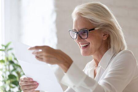 Sorridente donna d'affari invecchiata tenere documento cartaceo leggere buone notizie in corrispondenza, felice lavoratrice anziana guardare attraverso scartoffie sentirsi eccitata felicissima con lettera di approvazione o contratto Archivio Fotografico