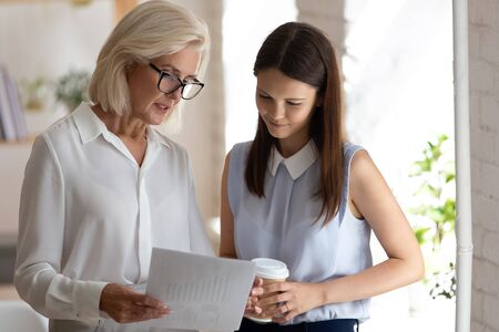 Diverse female employees stand discussing company financial statistics, woman banking specialists hold paper report cooperating talk consider paperwork stats, senior employer show graph to colleague