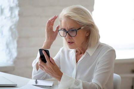 Confused senior businesswoman sit at office desk hold cellphone experience internet connection problem, frustrated aged woman worker feel disappointed having smartphone breakdown or virus attack Banque d'images