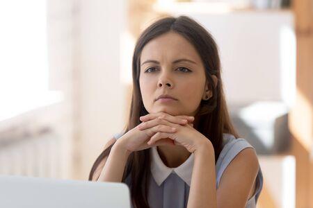 La giovane dipendente pensierosa si siede alla scrivania dell'ufficio pensando alla soluzione del problema, la lavoratrice millenaria premurosa si sente triste distratta dal lavoro meditando considerando idee o ricordando