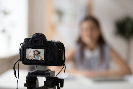 Professional camera shooting young smiling female tutor or coach making presentation or recording master class tutorial for channel, woman business vlogger filming video training for blog or website Standard-Bild - 129610448
