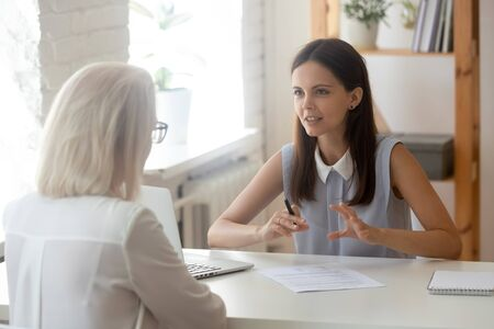 Focused millennial female talk with senior woman client consulting over contract or paper document, young recruiter or HR specialist speak with applicant or customer, have consultation in office