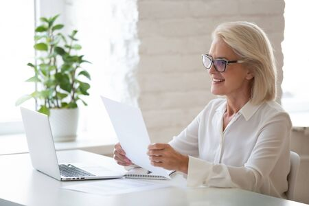 Smiling middle-aged woman in glasses sit at office desk work at laptop reading paper document, happy senior businesswoman in spectacles look through consider paperwork contract receive good news