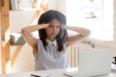 Exhausted overwhelmed female employee sit at office desk lose temper patience having deadline, tired young woman worker feel mad angry look at laptop screen lack motivation or ideas, nervous breakdown