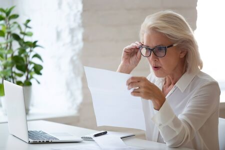 La lavoratrice anziana sorpresa con gli occhiali si siede alla scrivania dell'ufficio leggendo un documento cartaceo o un contratto si sente confusa con le cattive notizie, donna d'affari anziana frustrata stordita dalla corrispondenza dei documenti ricevuti Archivio Fotografico