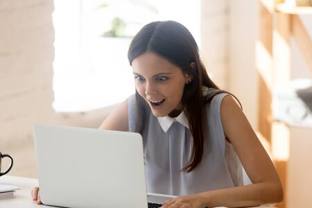 Excited young woman sit at desk look at laptop screen feel amazed stunned winning online lottery, overjoyed female using computer reading great amazing news, get job promotion email letter