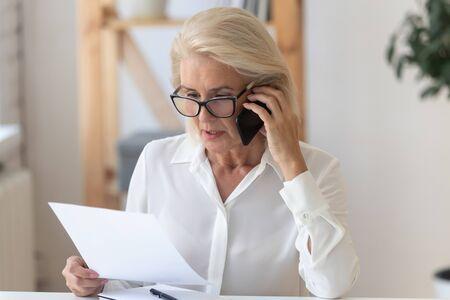 Konzentrierte ältere Geschäftsfrau mit Brille sitzt am Schreibtisch und spricht über das Handy, das Papierkramdokument liest, fokussierte Frau mittleren Alters spricht mit dem Kunden auf dem Smartphone und bespricht den Vertrag