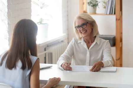 Happy senior businesswoman or consultant speak with millennial girl applicant having interview in office, smiling aged female boss or CEO talk with young woman candidate making good first impression Stockfoto - 129607097