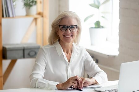 Portret van een gelukkige zelfverzekerde senior grijsharige zakenvrouw met een bril zit aan het bureau en kijkt naar de camera glimlachend, dolblij blije oude vrouw die een bril draagt en een foto maakt op de werkplek Stockfoto