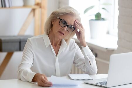 Pensive aged businesswoman in glasses sit at office desk thinking of problem solution, thoughtful senior woman worker in glasses look at laptop screen hold document pondering or making decision Stock Photo