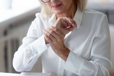 Crop close up of distressed aged grey-haired woman worker touch massage wrist suffering from hand spasm, stressed senior businesswoman having joint muscular pain or strain. Health problem concept Zdjęcie Seryjne