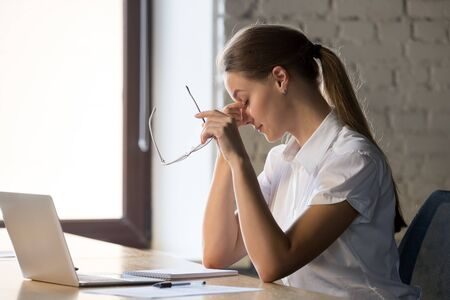 Tired businesswoman taking off glasses, suffering from eye strain, dry eyes syndrome after long laptop use, massaging nose bridge, exhausted employee sitting at desk, health problem concept