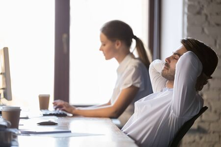 Peaceful businessman relaxing in comfortable office chair after finished work in office, sitting leaning back with hands behind head, daydreaming with closed eyes, enjoying break, no stress