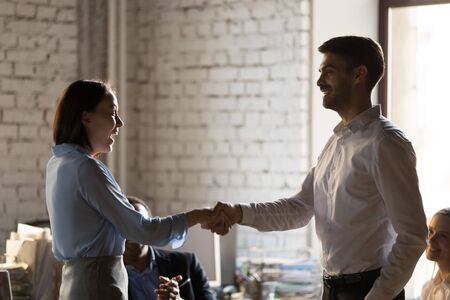 Smiling businessman boss shaking hand of successful employee at briefing, congratulating with job promotion, business achievement, team leader, executive thanking businesswoman for great work results