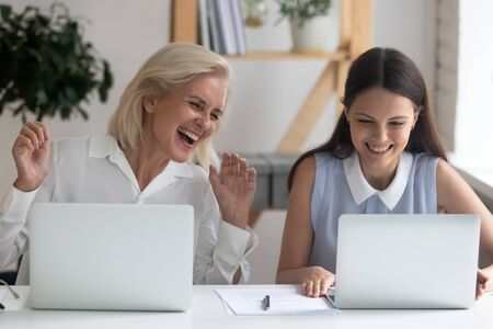 Overjoyed female employees sit at office desk have fun laughing working together at laptops, smiling happy woman workers enjoy break time using computers, watching funny video on gadget