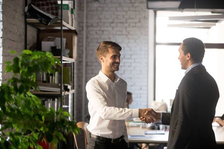 Smiling Caucasian businessman shaking hand of African American colleague, getting acquainted, newcomer introducing, first impression, friendly executive greeting new employee in office concept Фото со стока - 129607771