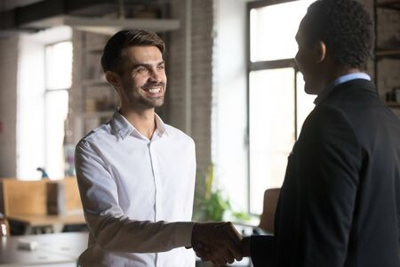Smiling employee handshaking with executive, getting job or reward, African American ceo, boss thanking successful businessman for good result, congratulating with promotion, respect concept