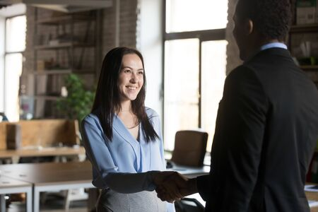 Smiling businesswoman handshaking with executive, getting job or reward, African American ceo, boss thanking successful employee for good result, congratulating with promotion, respect concept