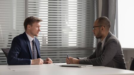 Two multiracial focused male partners holding business meeting at office, discussing company development strategy. Serious african american business owner discussing work issues with corporate client. Imagens