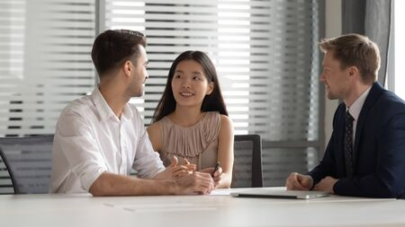 Smiling chinese young woman holding husbands hand, discussing house purchase, family savings investment. bank loan, mortgage, meeting bank manager, real estate agent, financial advisor at office. Imagens