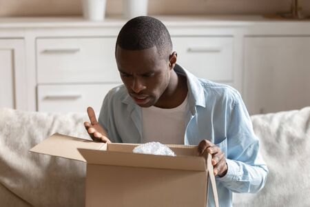 Frustrated mad african American man unpack cardboard box post shipping parcel with wrong order, disappointed male customer feel confused upset with poor quality and bad delivery service