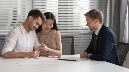 Happy young mixed race married spouse made decision about family savings investment, bank loan, mortgage or house purchase, buying consulting services, signing contract with bank manager in office.