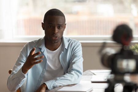 Motivated african American millennial male coach record video tutorial speech on professional cam, successful biracial man blogger talk with subscribers shooting vlog on camera at home Standard-Bild - 129608030