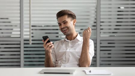 Cheerful successful motivated euphoric young manager using smartphone, received email with good news. Overjoyed millennial businessman celebrating online lottery bet win victory in mobile app.