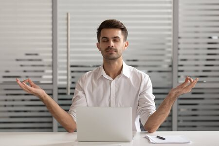 Mindful carefree millennial male manager meditating in office. Calm young employee sitting at workplace, making mudra gesture, deeply breathing with closed eyed, reducing stress and work pressure.