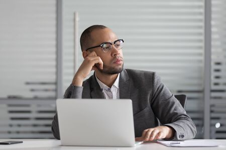 Thoughtful african american businessman in eyeglasses sitting at workplace, looking aside, thinking over problem solution. Pensive mixed race executive manager distracted from work lost in thoughts.