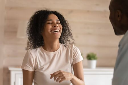 Overjoyed african American young wife laugh talking chatting with husband or friend, happy biracial millennial woman have fun smile have pleasant conversation with husband, communication concept Фото со стока