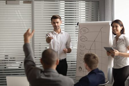 African american male manager raising hand, wishing to ask question about flip chart presentation of two happy mixed race male and female speakers at corporate training seminar at company office. Stockfoto
