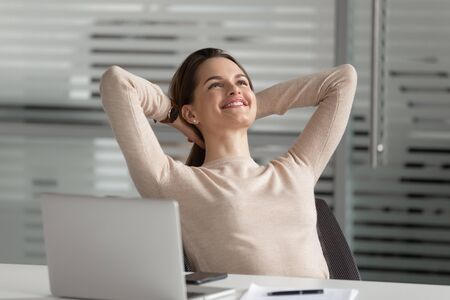 Smiling happy businesswoman leaning on comfortable chair, crossing hands behind hand, relaxing, having break at office. Peaceful female employee dreaming, visualizing future. No stress job concept.