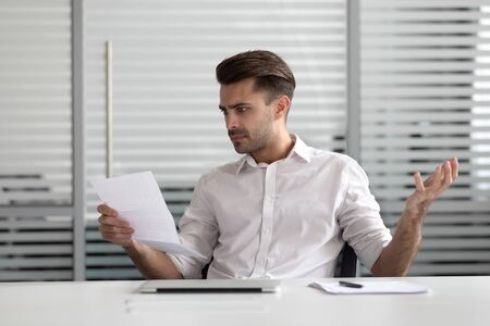 Annoyed young businessman holding paper, dissatisfied with unexpectedly bad financial project results, mistakes in document or disagree with information. Frustrated manager stressed by high bills. Imagens